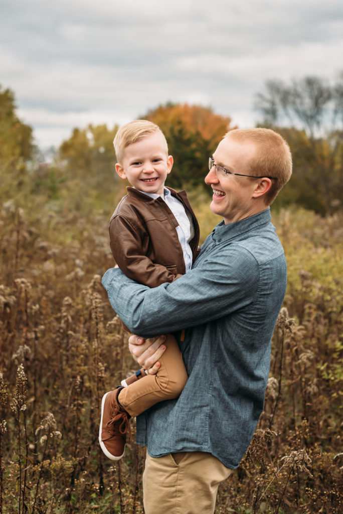 Family photograph, Father holds son in field, both smiling