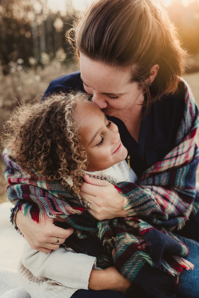Family portrait, Mother squeezes daughter tight outdoors, sun shines on them